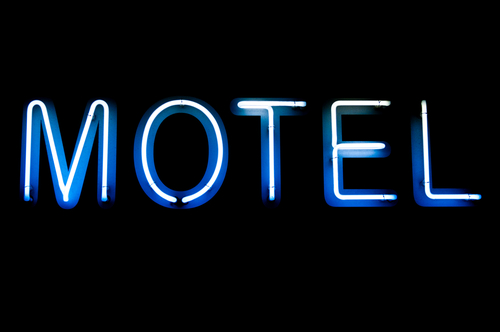 blue and white motel neon sign (isolated on black background)