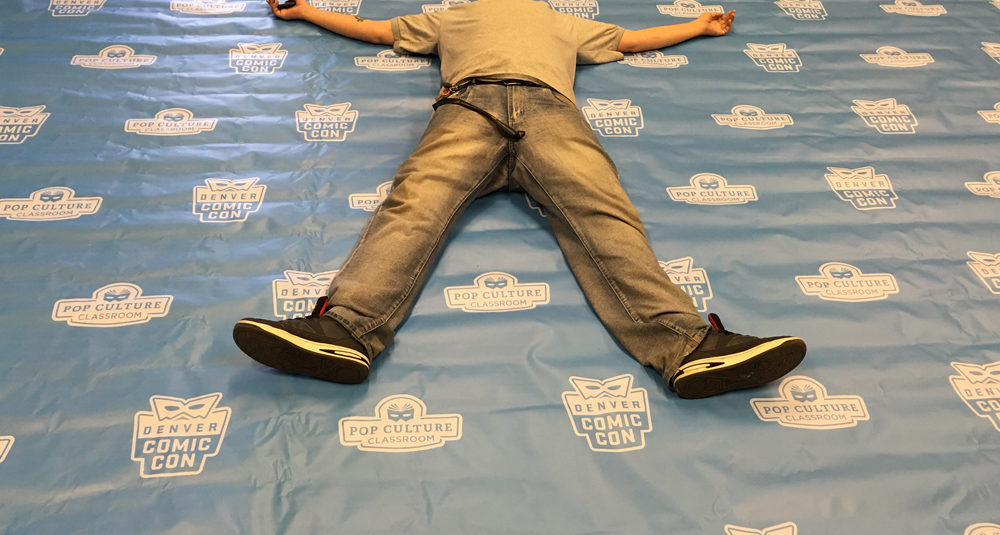 lance laying on denver comic con banner