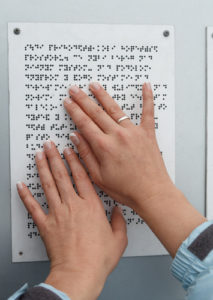 hands on a braille sign