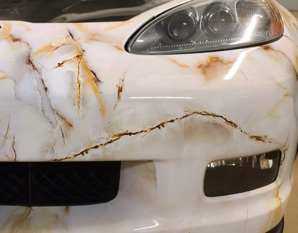 Full wrap of a corvette with marble pattern. Headlight view.