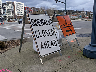 Angled view of Sidewalk Closed and Detour signs on a street corner