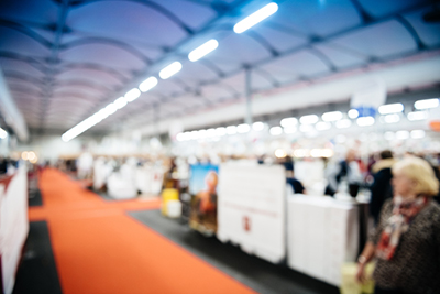 Defocused view of large hall with silhouettes of people visiting the exhibition fair with multiple booths