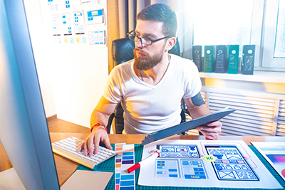 Ux ui design concept. The designer compares the paper layout of the mobile application with the web prototype. Prototyping software. Select the mobile application interface. Wireframing.
