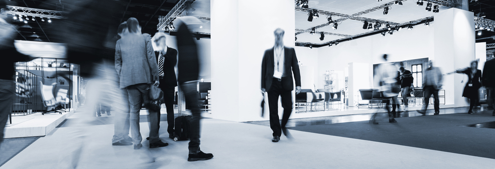 blurred business people rushing between Trade show Booths, banner size. ideal for websites and magazines layouts